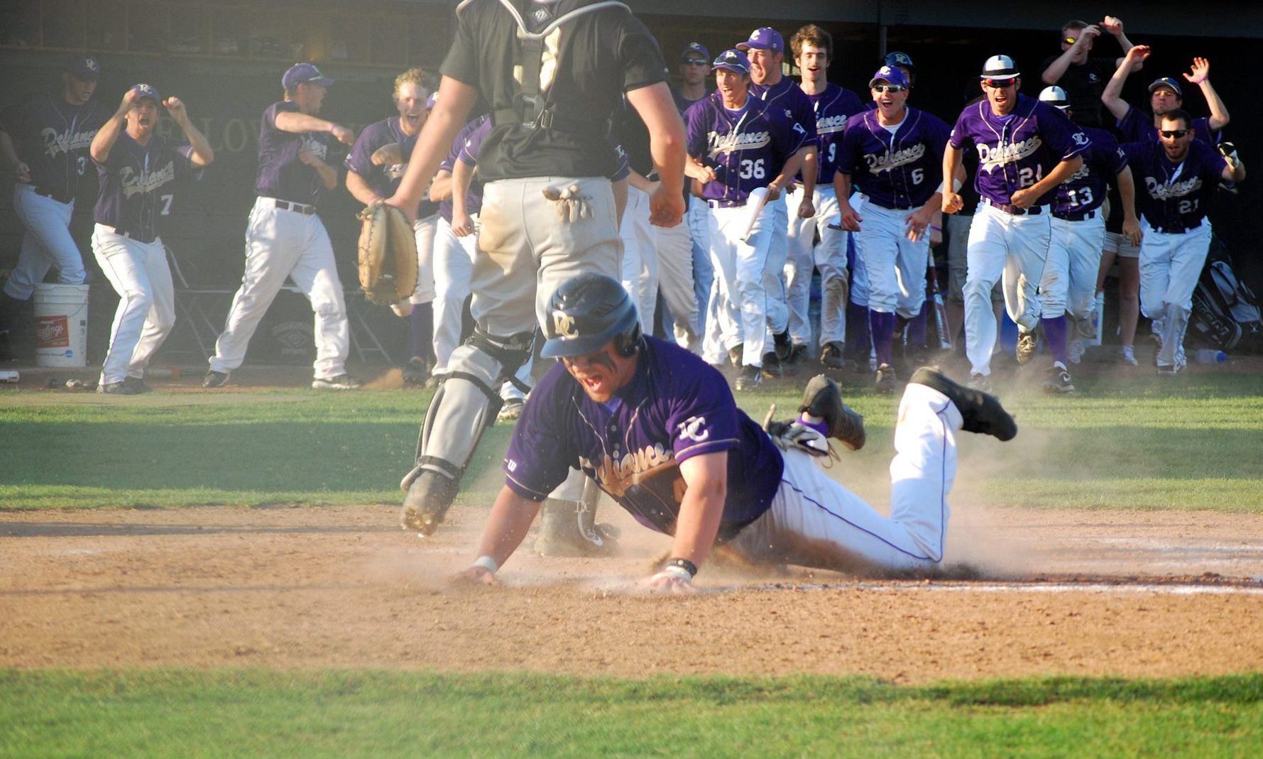 Defiance College baseball player sliding into home plate